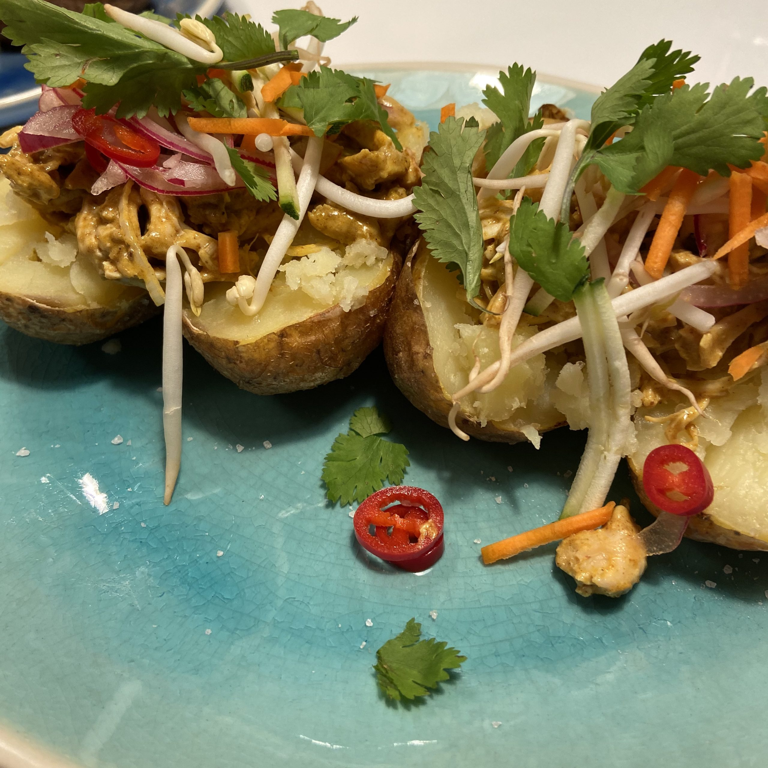 Gepofte aardappel met Thaise curry, pulled chicken, taugé en rode ui